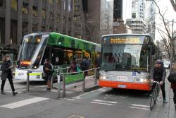 Transdev bus 6668AO on route 235 passes tram E2.6055 on route 96 at Bourke and William Street
