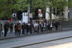 Passengers wait outside Southern Cross Station for the next bus to Fishermans Bend