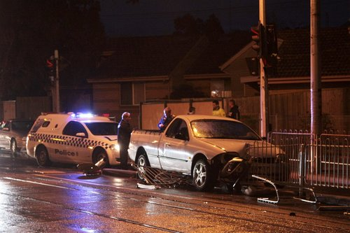 Police in attendance, looking over the ute impaled on five metres of tram safety zone fence
