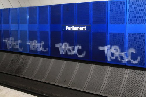 Tags spray painted along the walls at Parliament station