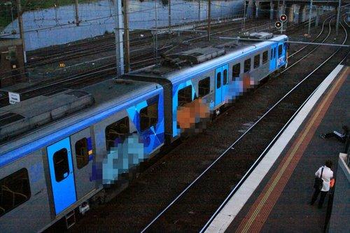 Siemens train in service, running around with three graffiti murals on the side