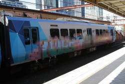 X'Trapolis train in service with a pair of graffiti murals on the side
