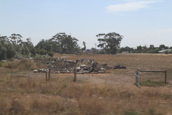 Opened gates and piles of dumped rubbish beside the Regional Rail Link tracks in Truganina