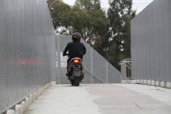 Riding a petrol scooter over the pedestrian bridge at St Albans