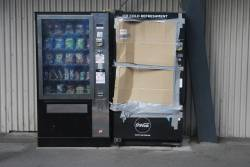 Smashed vending machine covered up with cardboard at North Melbourne station