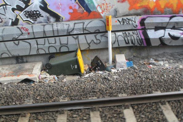 Wheelie bin and office chair lay abandoned at the bottom of the Footscray railway cutting