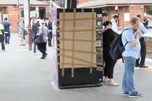 'EMPOTY' scrawled across a damaged vending machine patched up with cardboard at North Melbourne station