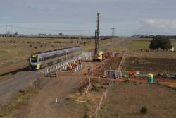 Six-car VLocity consist on an up Ballarat service passes construction at the new Caroline Springs station
