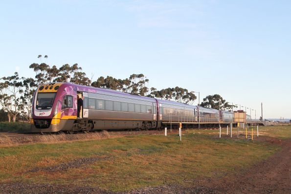 Six car VLocity train overhangs the short platform at Rockbank by a carriage length