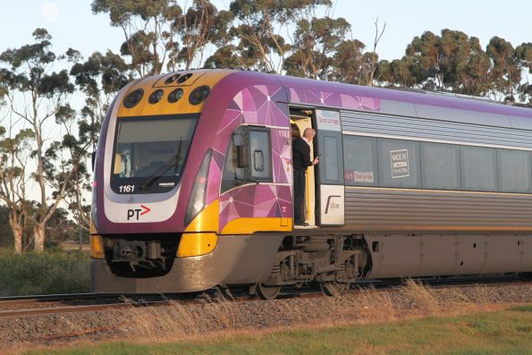 Conductor of an up Ballarat service hangs out of the open door at Rockbank to watch passengers board