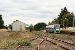 VLocity VL09 departs Ballan on the down, passing the remains of the yard and a disused goods shed
