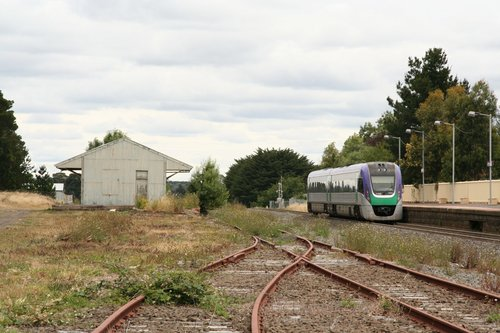 VLocity train departs Ballan on the down, passing the remains of the yard and a disused goods shed
