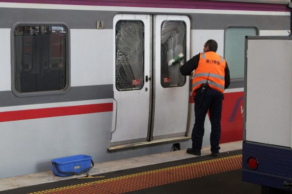 V/Line cleaning staff washing windows of a carriage set
