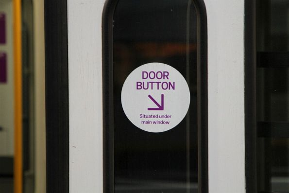 'Door button situated under main window' sticker on the door of a Sprinter train
