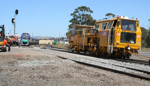 VLocity train passes a ballast tamper on the other track at North Shore
