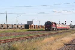 N461 departs North Shore, passing log flats and standard gauge NSW NGPF/NGKF grain hoppers