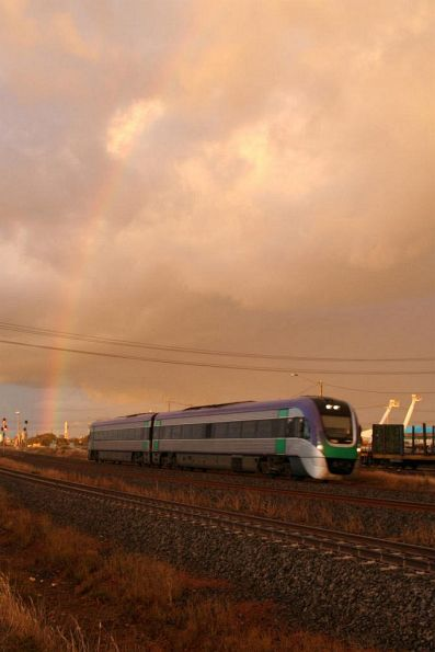 Vlocity on the down at North Shore under a rainbow and fire reddened sunset