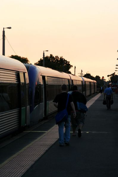 Commuters under a red sunrise at South Geelong