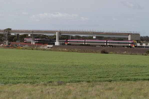 Up Geelong service passes beneath the new Regional Rail Link flyover at Manor Junction