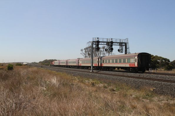 N469 leads a mixed liveried consist on an up Warrnambool service at Manor