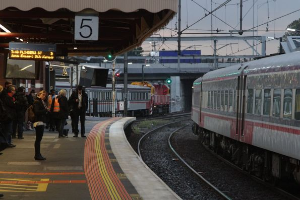 N class leads a citybound service out of Footscray on the RRL tracks, as a down Warrnambool service stops at platform 6