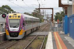 Crawling along behind a suburban train, VLocity VL63 passes through Murrumbeena station