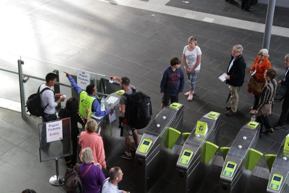 Passengers with paper tickets waiting to exit the platform, as the sole V/Line staff member on the ground having to assist other passengers with directions