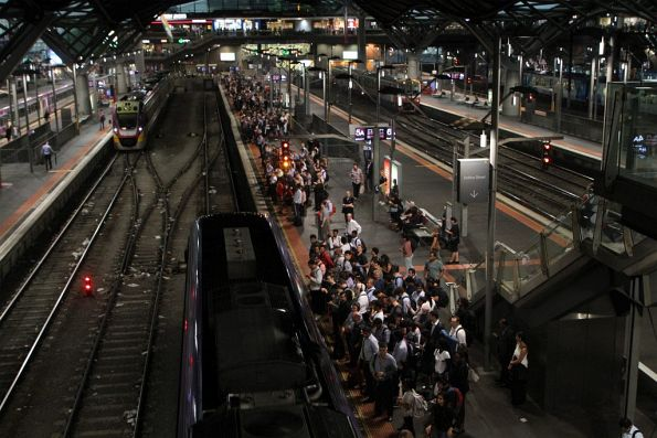 Geelong line passengers wait as their late running train finally arrives into the platform at Southern Cross