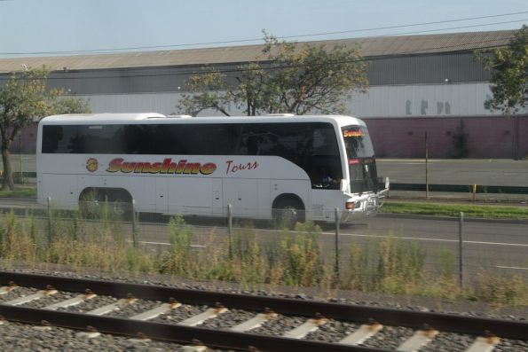 Sunshine Tours road coach parallels the Regional Rail Link tracks at Tottenham
