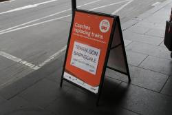 'Traralgon & Bairnsdale coaches departure here' sign outside Flinders Street Station
