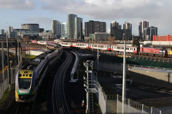 VLocity heads for Southern Cross on the new RRL tracks, as a push-pull H set descends the North Melbourne flyover