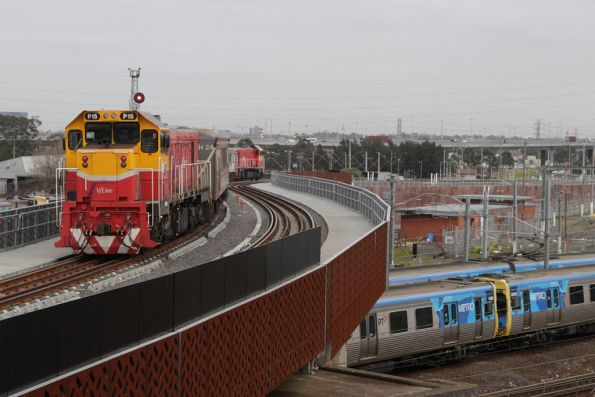 Outbound V/Line service crosses the North Melbourne flyover, as a pair of suburban trains pass beneath