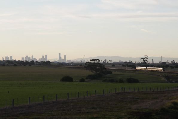 CBD skyline in the background as a 5-car down Geelong service approaches Tarneit