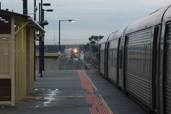 Doors close on the departing VLocity at Deer Park station, as the next train closes in