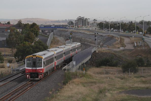 Sprinter 7021 and four classmates crawl out of Wyndham Vale minus passengers, bound for the Wyndham Vale South turnback siding