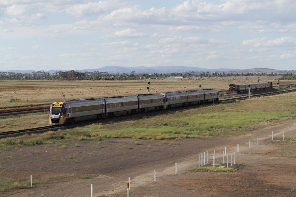 Down Geelong service passes a push-pull consist sitting in the turnback siding at Wyndham Vale South