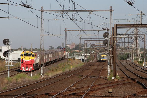 P15 leads a push-pull consist along the RRL tracks, as a Comeng follows close behind on the parallel suburban lines