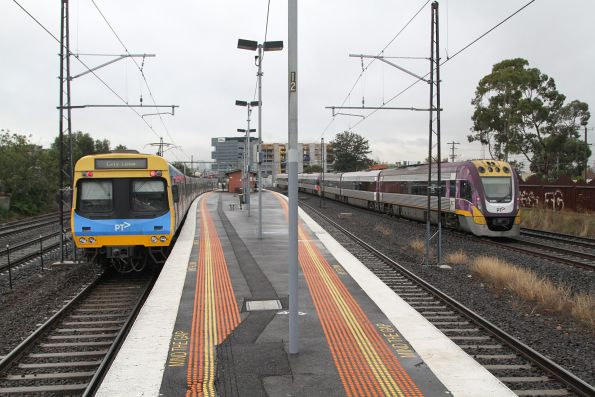 Comeng train departs Middle Footscray on the up, as a VLocity train speeds past on the RRL tracks
