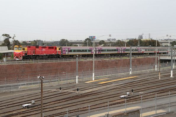 N451 heads over the North Melbourne flyover with a mixed liveried carriage set