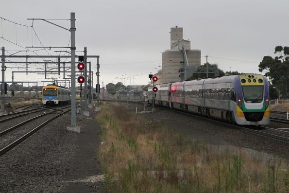 VLocity VL20 chases down a suburban train on the parallel tracks at Sunshine