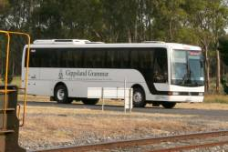 Dysons bus in 'Gippsland Grammar' livery on a V/Line service, waiting for H4 leading the up Maryvale goods out of the mill outside Morwell
