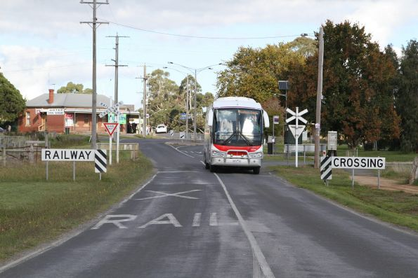 V/Line liveried Westernport Road Lines coach #66 8816AO crosses the disused South Gippsland line at Nyora with a Melbourne-bound service