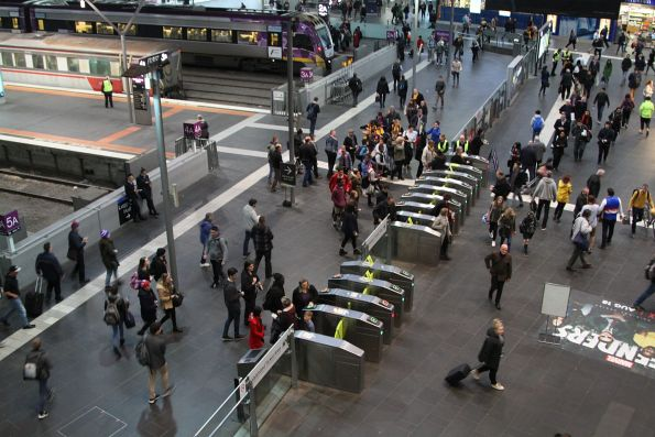 Crowd of arriving passengers queue to exit the country platforms at Southern Cross