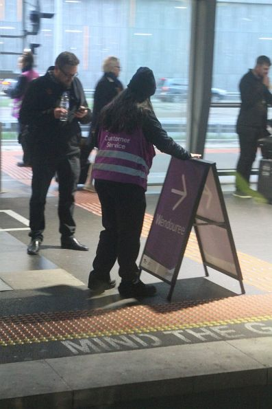 V/Line staff swap over the departure A-frame boards at Southern Cross platform 15