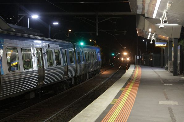 Comeng train waits at Footscray station, as a citybound Geelong service approaches via the suburban tracks