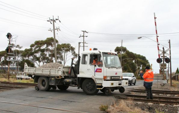 Putting down the rail wheels of a hi-rail truck at the St Georges Road level crossing at North Shore