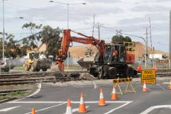 Excavator digging out the old road surface at the Station Street level crossing at North Shore