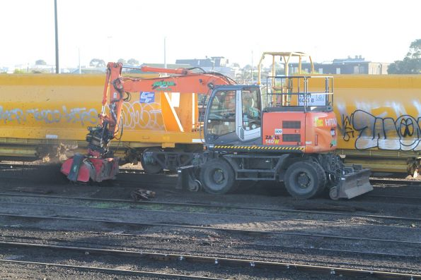 Hi-rail excavator at work cleaning up the ballast following sleeper replacement at Tottenham Yard