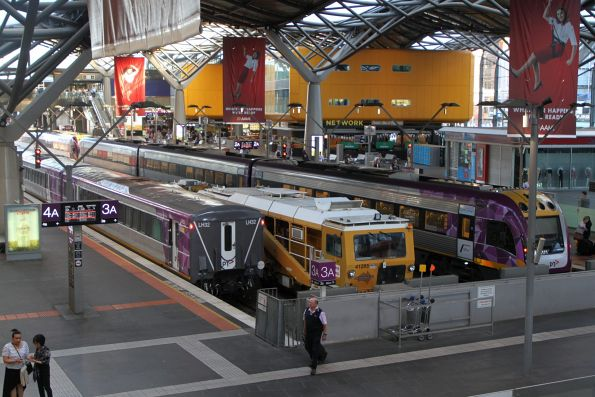 Ballast tamper and regulator stabled among V/Line trains at the south end of Southern Cross platform 2 and 3