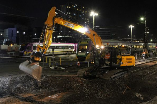 Excavator loads sleepers and spoil into a dump truck at Southern Cross Station